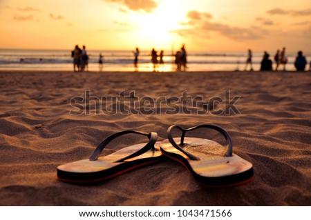 Beautiful capture of flip flops in the sand on Seminyak beach, Bali, Indonesia