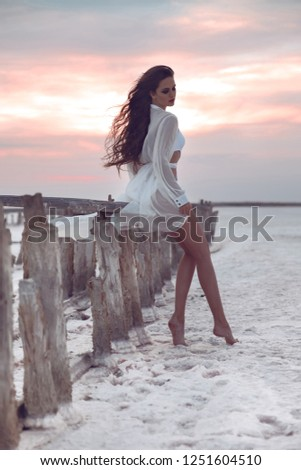 Beautiful care free confidence woman in white swimsuit enjoy summer vacation at sunset on salty beach. Carefree brunette girl posing in white swimwear enjoying freedom.  #1251604510