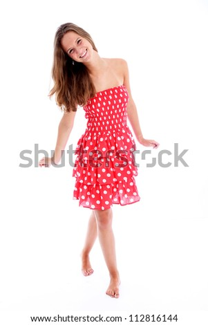 Beautiful carefree barefoot teenager Beautiful carefree barefoot teenager with a vivacious smile walking across the frame in a pretty red and white polka dot sundress