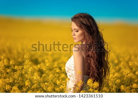 Beautiful carefree girl with long curly healthy hair over Yellow rape field landscape background. Attracive brunette with blowing hairstyle enjoying sunset, outdoor beauty portrait.  #1423361510