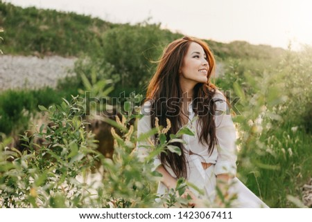 Beautiful carefree long hair asian girl in the white clothes on river side in grass at sunset. Sensitivity to nature concept #1423067411