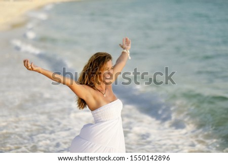 Beautiful carefree woman with arms outstretched enjoying in freedom in summer day at the beach.   #1550142896