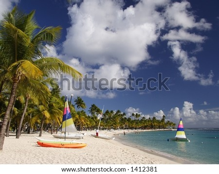 Beautiful caribbean beach with a colorful jolly boats and kayaks