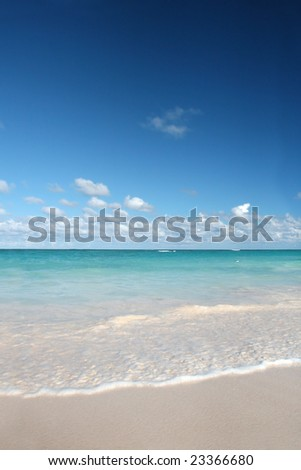 Beautiful Caribbean tropical beach with white sand and green ocean, suitable background for a variety of designs. FOCUS on edge of waves rolling onto the beach