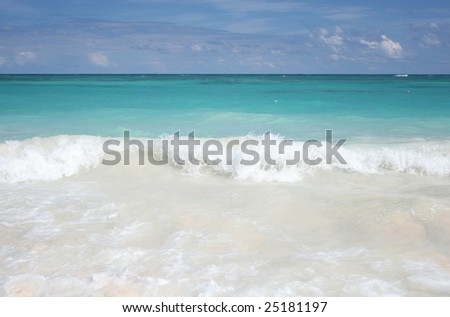 Beautiful Caribbean tropical beach with white sand and green ocean, suitable background for a variety of designs (focus on waves rolling onto shore)
