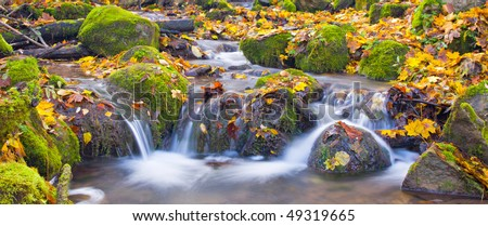 beautiful cascade waterfall in autumn forest - stock photo