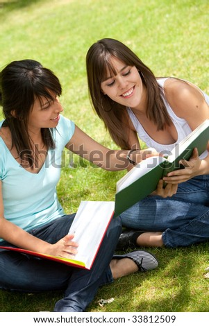 Beautiful casual girls studying with notebooks outdoors