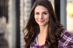 Beautiful casual natural brunette commercial model portrait close up headshot with dimpled grin