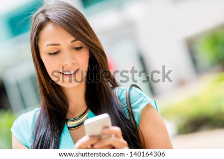 Beautiful casual woman texting on her cell phone