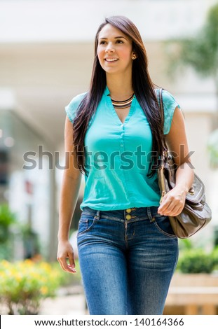 Beautiful casual woman walking outdoors and looking happy