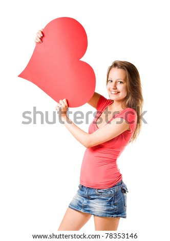 Beautiful casually dressed smiling happy young brunette girl holding large red heart shape, isolated on white background