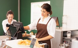Beautiful caucasian barista woman making coffee orders on cashier machine at the coffee bar in cafe coffee shop. Barista work at coffee bar and food service business