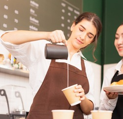 Beautiful caucasian barista women fill white milk into takeaway hot coffee cup at coffee bar in cafe coffee shop. Barista work at coffee bar and food service business