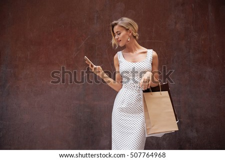 Beautiful caucasian blonde female wearing white summer dress with black polka dots is looking at the screen of the mobile phone while standing on a dark brown background with a blank paper bags. #507764968