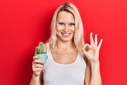 Beautiful caucasian blonde woman holding small cactus pot doing ok sign with fingers, smiling friendly gesturing excellent symbol