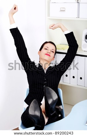 Beautiful caucasian businesswoman with legs laying on the desk stretching in the office.