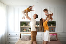 Beautiful Caucasian family with two children in their arms, dad and mom hold two children in the air, a real bright Scandinavian-style interior
