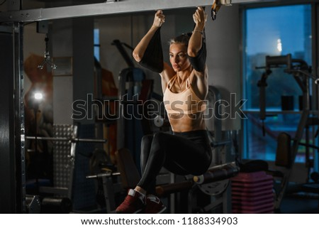 Beautiful caucasian fitness woman training with trx fitness straps. Suspension exercising in gym. Stock foto ©
