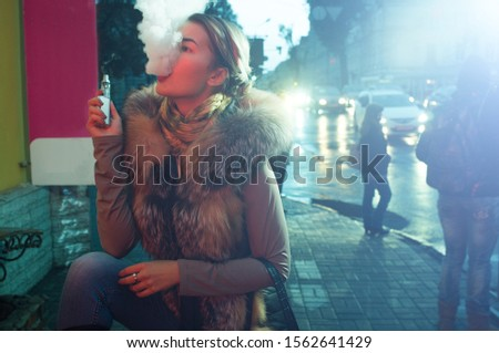 Beautiful caucasian girl in winter clothes on the street, she has jacket's fur,she smokes an electronic cigarette, vaping out smoke with a self confident gesture, illuminated by a street's ads panel Stock fotó ©