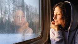 Beautiful caucasian girl looks at nature through the train window, 4k.