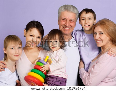 Beautiful Caucasian happy family standing on a purple background