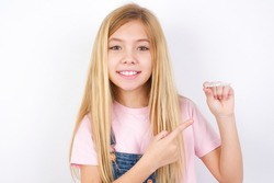 beautiful caucasian little girl wearing jeans overall over white background holding an invisible aligner and pointing at it. Dental healthcare and confidence concept.