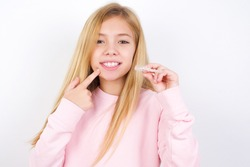 beautiful caucasian little girl wearing pink sweater over white background holding an invisible aligner and pointing to her perfect straight teeth. Dental healthcare and confidence concept.