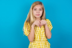 beautiful caucasian little girl wearing yellow dress over blue background makes bunny paws and looks with innocent expression plays with her little kid