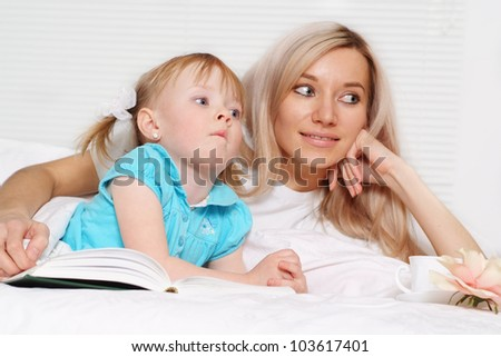 Beautiful caucasian mum and daughter lying on the bed with a book