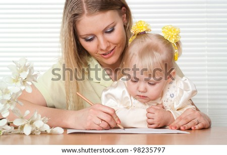 Beautiful Caucasian mummy and daughter sitting at a table near the window
