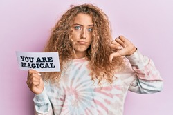 Beautiful caucasian teenager girl holding you are magical banner with angry face, negative sign showing dislike with thumbs down, rejection concept