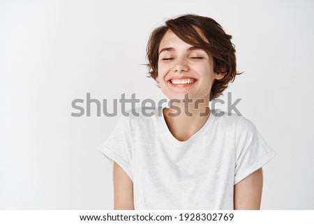 Beautiful caucasian woman dreamy smiling with eyes closed, standing relaxed and happy against white background. Copy space Foto stock ©
