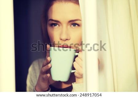 Beautiful caucasian woman drinking hot coffee or tea