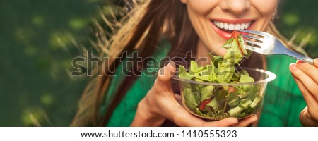 Beautiful caucasian woman eating salad over green natural background