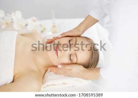Beautiful caucasian woman enjoying facial massage with closed eyes in spa salon. Relaxing treatment in medicine and Beauty concept