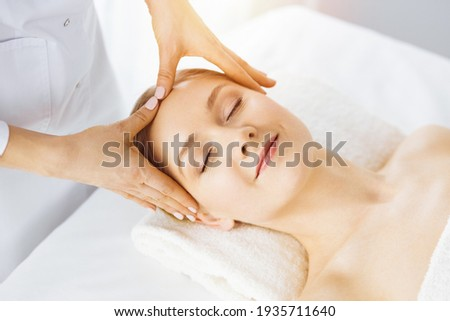 Beautiful caucasian woman enjoying facial massage with closed eyes in sunny spa salon. Relaxing treatment in medicine Foto stock ©