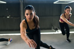 Beautiful caucasian woman exercising in the gym with high-intensity interval training. Two fit women doing lateral bounds