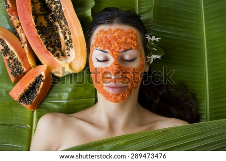 Beautiful caucasian woman having fresh papaya natural facial mask apply, skin care and wellness (outdoors). Facial vitamin mask of papaya slices at spa salon