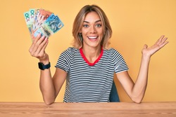 Beautiful caucasian woman holding australian dollars celebrating achievement with happy smile and winner expression with raised hand