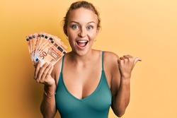 Beautiful caucasian woman holding bunch of 50 euro banknotes pointing thumb up to the side smiling happy with open mouth