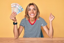 Beautiful caucasian woman holding canadian dollars screaming proud, celebrating victory and success very excited with raised arm