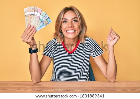 Beautiful caucasian woman holding canadian dollars screaming proud, celebrating victory and success very excited with raised arm  Photo stock ©