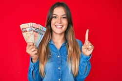 Beautiful caucasian woman holding canadian dollars smiling with an idea or question pointing finger with happy face, number one