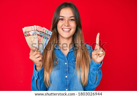 Beautiful caucasian woman holding canadian dollars smiling with an idea or question pointing finger with happy face, number one  Stockfoto ©