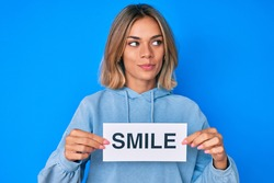 Beautiful caucasian woman holding smile text smiling looking to the side and staring away thinking.