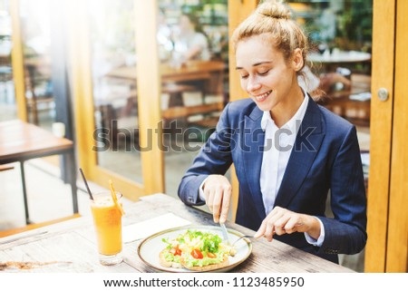 Beautiful caucasian woman in formals eating avocado sandwich in a cafe #1123485950