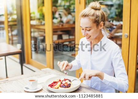 Beautiful caucasian woman in formals eating pancakes in a cafe #1123485881