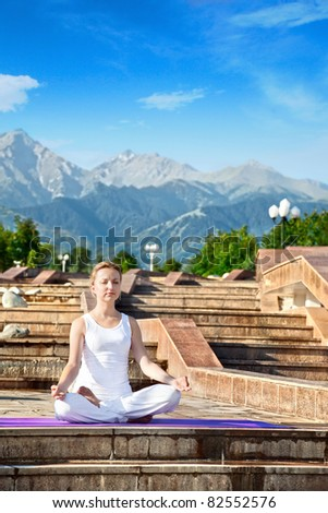 Beautiful Caucasian woman in white cloth doing meditation in ardha padmasana, half lotus pose with dhyana mudra gesture. Woman Sitting on the stone stairs at Mountain background