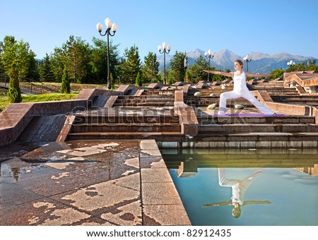 Beautiful Caucasian woman in white cloth doing virabhadrasana II, warrior pose with reflection in water and mountains, blue sky at background