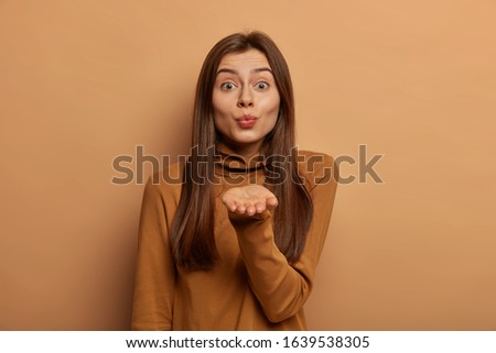 Beautiful Caucasian woman pouts lips, sends air kiss, keeps palm extended, expresses love and affection, demonstrates feelings, wears brown turtleneck, looks sincerely at camera, stands indoor